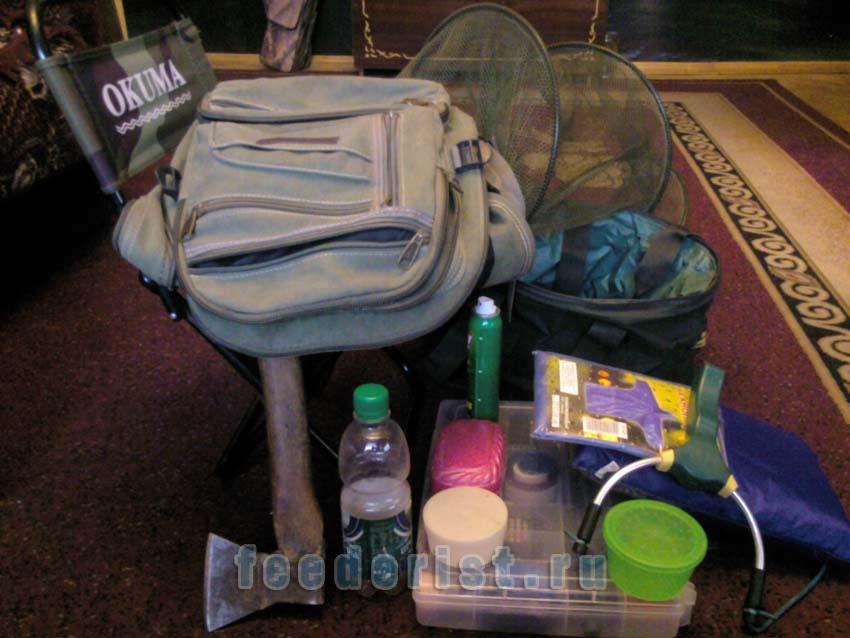 Содержимое рюкзака - стул, ведро, садок, коробка с принадлежностями, топор, бутылка, коробки для наживки, рогатка, мыло, полотенце, средсво от комаров, плащ (синий пакет).